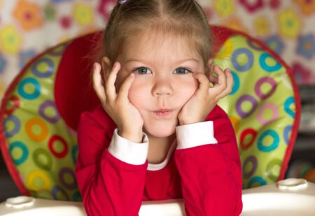 portrait of thinking and sad little girl propping head by hands looking at camera Stock Photo