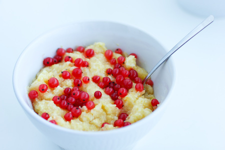 Homemade healthy maize porridge with red currant in white bowl on the table Stock Photo