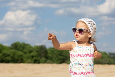 Little girl in sunglasses pointing finger hand aside and looking aside