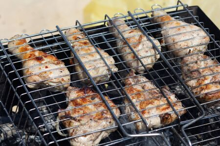 Grilled parts of chicken on the grill cooking on smoldering coal