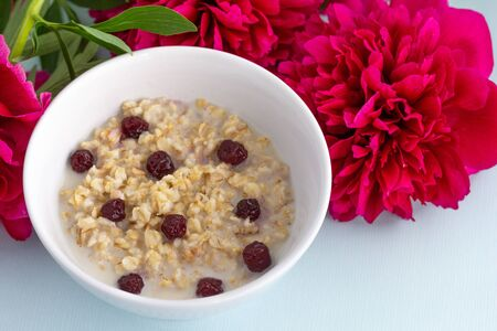 Bowl of oatmeal porridge with frozen cherries on white background with pionies