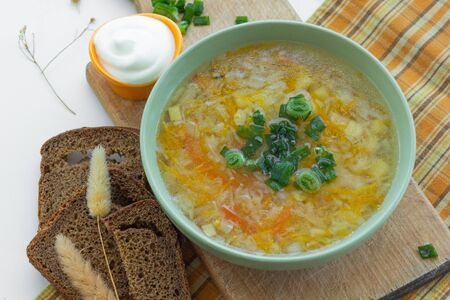 Traditional soup of Russia Shchi with green onion served with sour cream as garnish and bread Stock fotó
