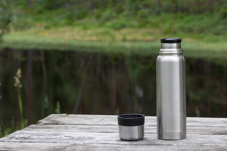 Thermos and cup on wooden table in forest near lake