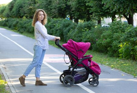 Young mother with newborn in stroller 스톡 콘텐츠