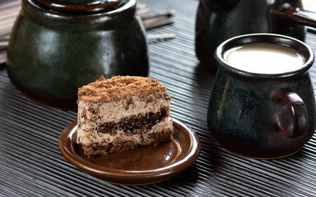 Piece of cake, cup of cofee and fresh milk on the wooden table