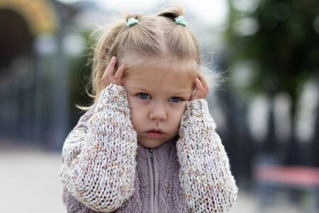 Child holding her head by hands feeling stress Stock Photo