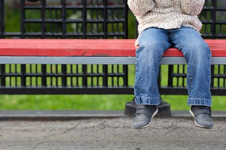 Child legs dangling from bench with copy space