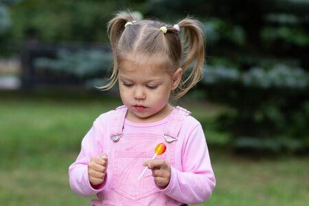 Beautiful child with lollipop in summer park