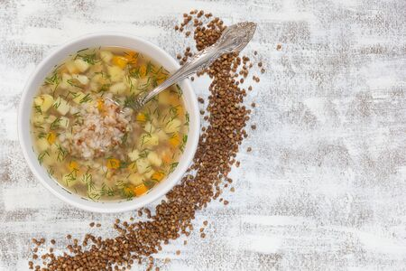 Top view of buckwheat soup in white bowl on the white background Stock Photo