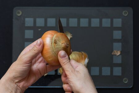Top view of woman hand cutting onion with the knife