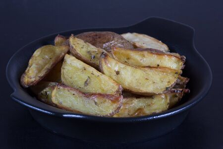 Close up rustic roasted potatoes on black plate on the black background Stock Photo