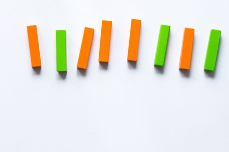 Multicolored toy sticks blocks lying in row on white background