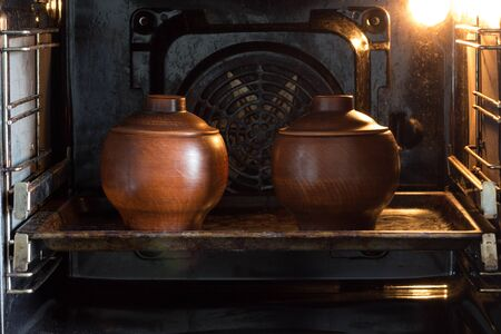 Two clay pots on the pan in the oven