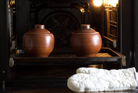 Two clay pots on pan in oven and white potholders