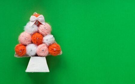DIY christmas tree made from woolen threads on green background Stock Photo