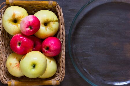 Apples and empty glass dish for baking on the wooden background