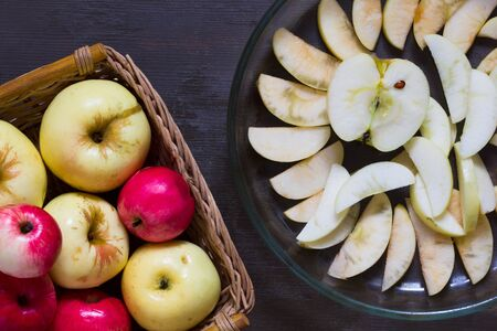 Apples and glass dish for baking with cutting apples on the wooden background
