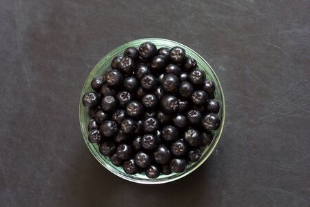 Top view of chokeberries in glass bowl on the black background