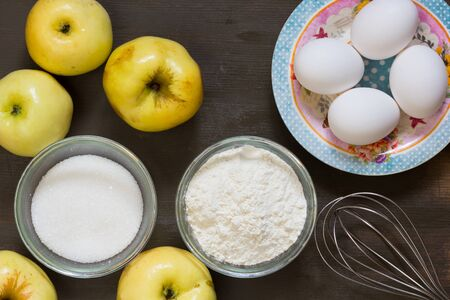 Top view of apples, eggs, sugar, flour and whisk on the wooden background Stock Photo