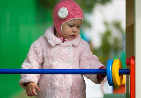Little girl playing with wooden toy counter outside Stock Photo