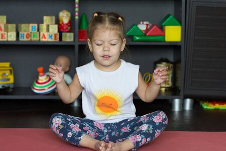 Cute little girl sitting in yoga pose with closed eyes indoor