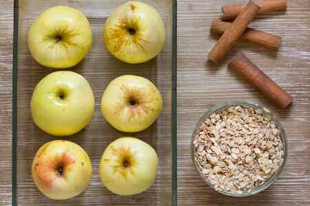 Top view of apples oats cinnamon sticks as ingredients for baked apples on the wooden background