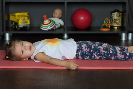 Little girl lying on the mat indoor before physical training