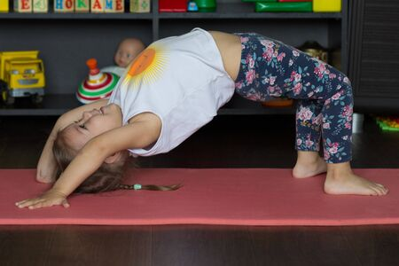 Little girl getting up in bridge making physical training indoor