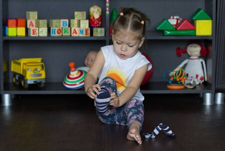 Little girl putting on socks sitting on floor indoor Stock Photo
