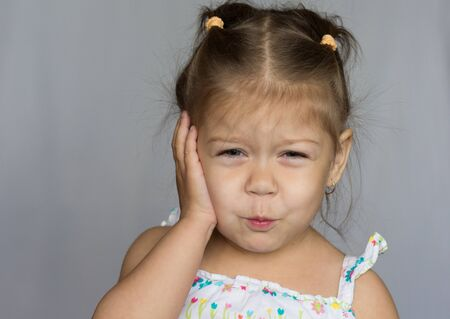 Portrait of little girl showing toothache on white background