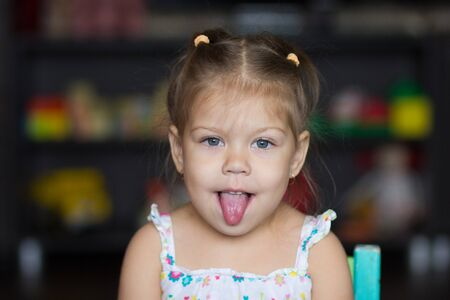 Portrait of cute little girl Portrait of cute little girl showing tongue looking at camera Stock Photo