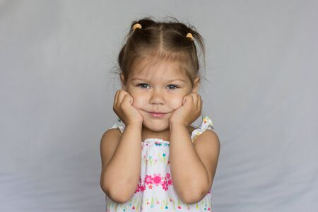 Happy child holding her cheeks by hands on white background Stock Photo