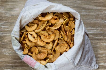 Top view of dry brown apples in white bag on the wooden background