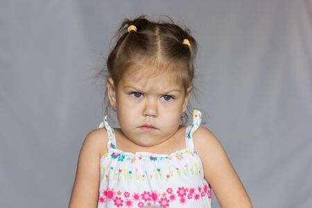 Portrait of very angry little girl on white background