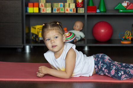 Little girl lying on mat indoor before physical training Stock Photo