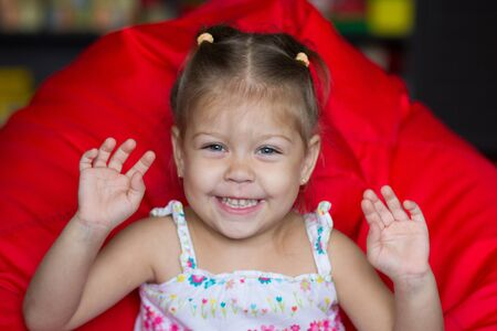 Portrait of laughing little girl sitting on red armchair Stock Photo