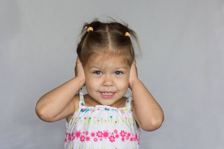 Smiling child does not want to hear anything closing her ears by hands