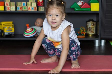 Little girl sitting on mat indoor before physical training