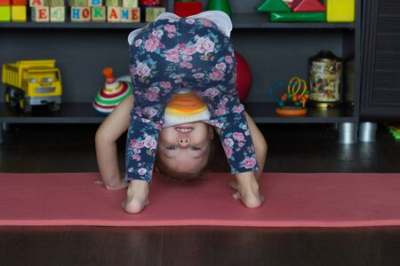 Little girl bending down making physical training indoor Stock Photo