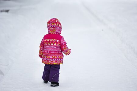 Back of child in snowy park in winter Stock Photo