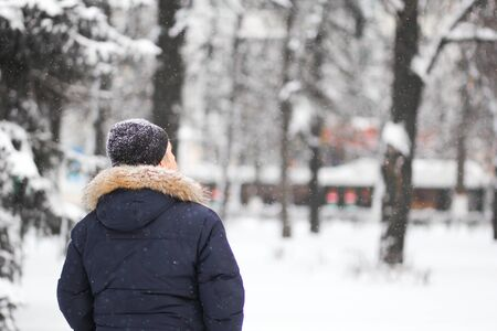 Back of man looking up in the snowy park in winter Stock Photo