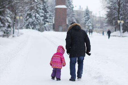Back of man and child going away in the snowy park in winter