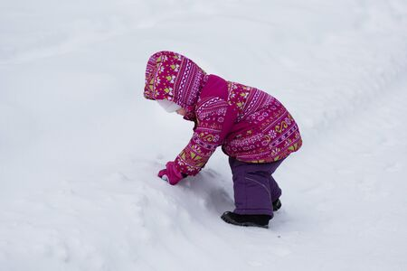 Child playing with snow in the snowy park in winter Stock Photo