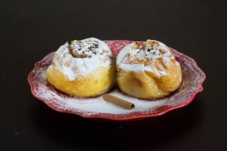 Two baked apples filled oats and powdered by sugar powder on red plate on the black background Stock Photo