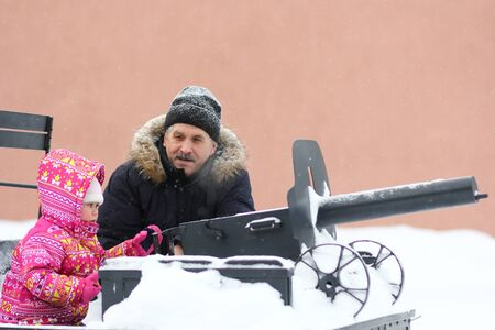 Mature man and little girl on tachanka monument in snowy park in winter