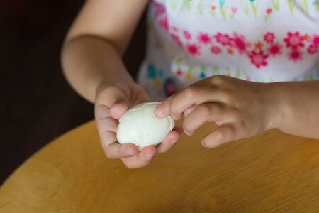 Hand of child peeling cooked egg pulling off shell