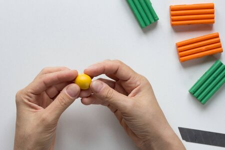 Woman hands holding small yellow ball made from polymer clay on the white background