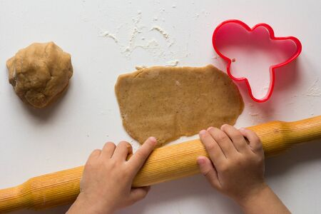 Rolling out gingerbread dough by child hands on the white background