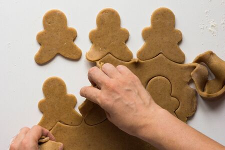 Excess of gingerbread dough removing from rolled out and cutted dough by woman hand on the white background
