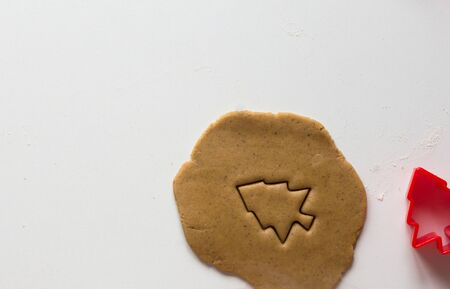 Cutted form of christmas tree on rolled out gingerbread dough on the white background